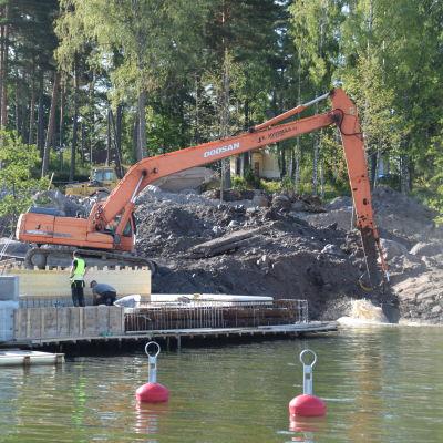 En orange grävskopa jobbar i en hamn. Byggjobbare syns i närheten av grävskopan.