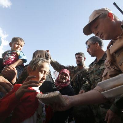 En rysk officer delar ut mat till syrier.