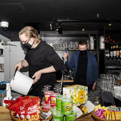 Ravintolapäällikkö Esa Kvist kuivasi lattiaa, vuoropäällikkö Tuomas Kolu tyhjensi hanasta valutetun tuotteen viemäriin.