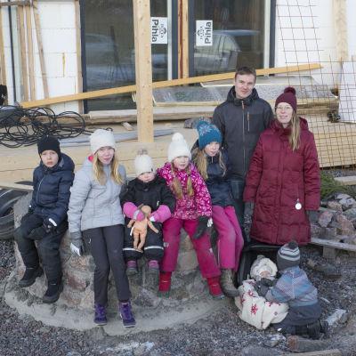 Mäkelän perhe poseeraa keskeneräisen omakotitalonsa edessä.