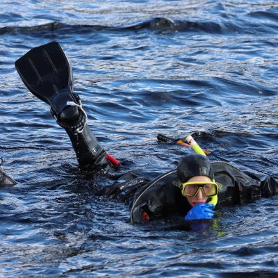 Metsähallituksen suunnittelija Miina Auttila on märkäpuku päällä ja räpylät jalassa snorklaamassa havaintoja norpan pesinnästä.