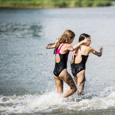Tre barn springer i vattnet.