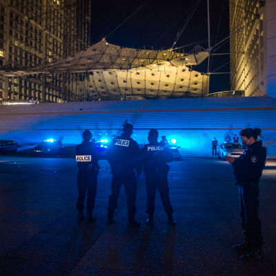 En rad poliser i förgrunden och polisbilar med blåljus i bakgrunden.