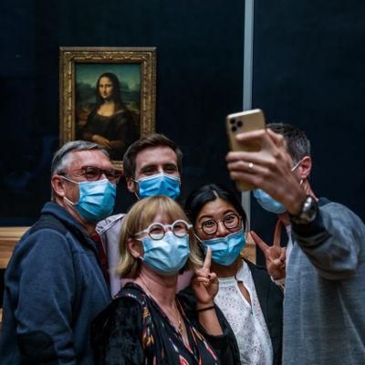 Joukko turisteja kasvomaskeissa poseeraa kuvattavana Mona Lisan edessä.