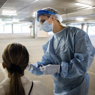 En sjukskötare tar ett coronatest på en kvinna.
