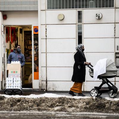 En kvinna i munskydd går med barnvagn i Helsingfors.