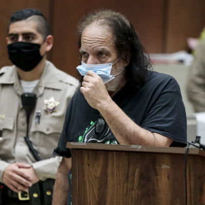 Pornotähti Ron Jeremy kasvomaski päällään oikeussalissa.