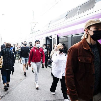 Många människor med munskydd på Helsingfors järnvägsstation.