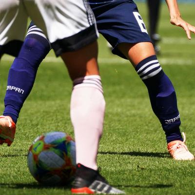 Närbild på två fotbollsspelares ben.