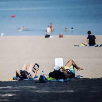 Människor njuter av solen på Sandudds badstrand i Helsingfors.