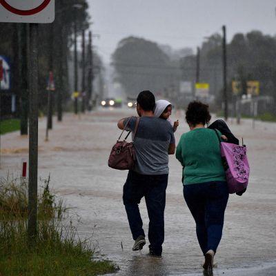 Invånare traskar genom en översvämmad väg under kraftigt regn i västra Sydney den 20 mars 2021.