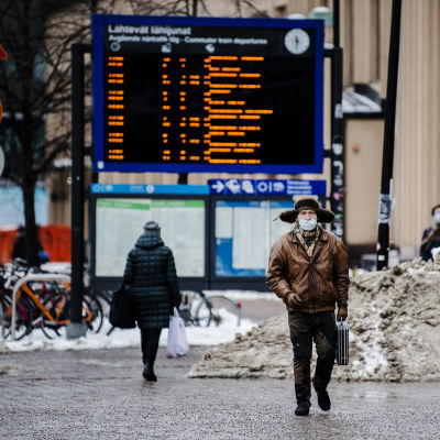 En man i pälsmössa utanför järnvägstationen i Helsingfors. Han har en portfölj i handen. Bakom honom finns en elektronisk tavla där man ser vilken tid tågen avgår och anländer..