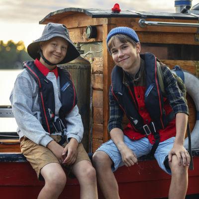 Kaksi poikaa istuu veneen laidalla, katsoo kameraan ja hymyilee.