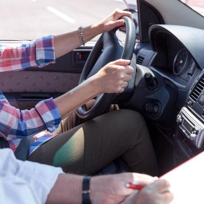 Bild på person som kör bil medan en annan gör anteckningar bredvid.