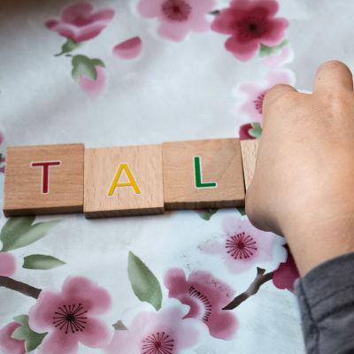 Ett barns hand som lägger träbitar med bokstäver i ordningsföljd.