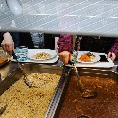Två elever tar åt sig mat i ett skolkök.