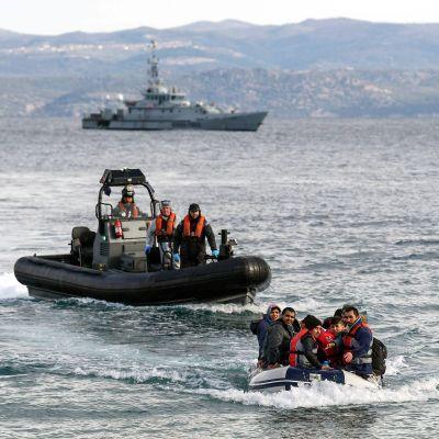 En större gummibåt med tre gränsbevakare åker bakom en mindre, fullsatt gummitbåt.