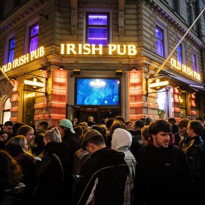 Massa människor som trängs utanför dörren till en pub i centrala Helsingfors.