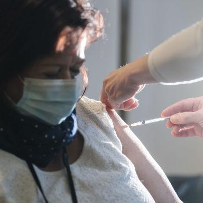 En person får coronavaccinet i Helsingfors i början av januari 2021.