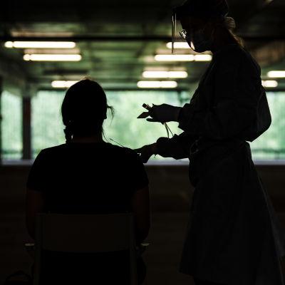 En sjukskötare tar ett coronatest av en person på ett drive-in-ställe.