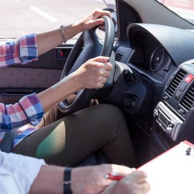 En person lär sig köra bil.