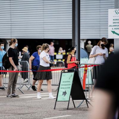 Personer köar utanför mässcentret i Helsingfors för att bli vaccinerade.
