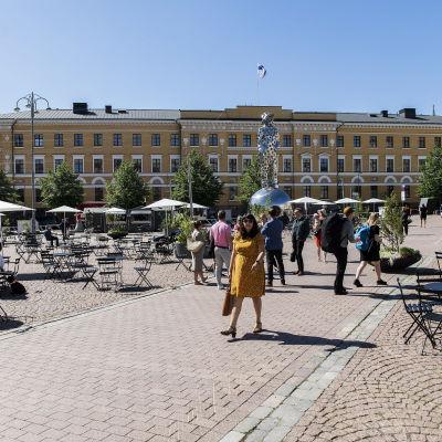 Personer på kaserntorget i Helsingfors och uteservering med koronasäkra avstånd.
