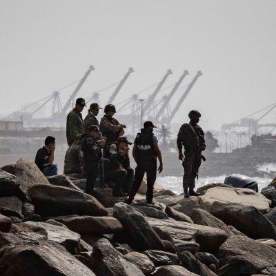 Sotilaita seisomassa rantakivikossa.