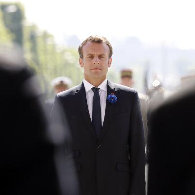 Frankrikes president Emmanuel Macron syns mellan två kostymbeklädda axlar under högtidligheter för att uppmärksamma att det gått 73 år sedan segern över Nazityskland.