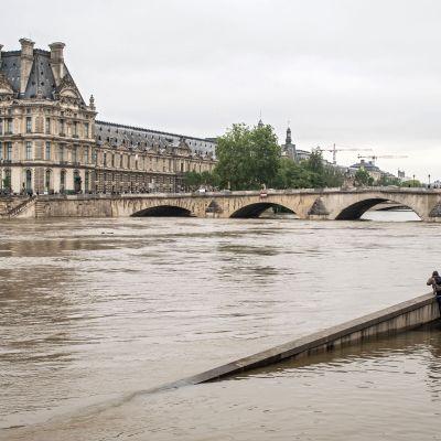 Seinejoki, jossa pinta noussut, joen takana Louvren taidemuseo. Etualalla joitakin ihmisiä katselemassa ja ottamassa kuvaa.