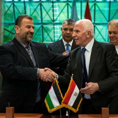 Hamas vice-ledare Saleh al-Aruri skakar hand med Fatahs representant Azam al-Ahmed efter att ha undertecknat gruppernas försoningsavtal efter en 10 år lång konflikt.
