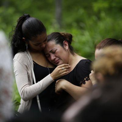 nainen itkee hautajaisissa, joissa audataan nuorta opiskelijaa