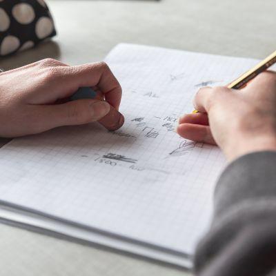Opiskelija kirjoittaa vihkoon