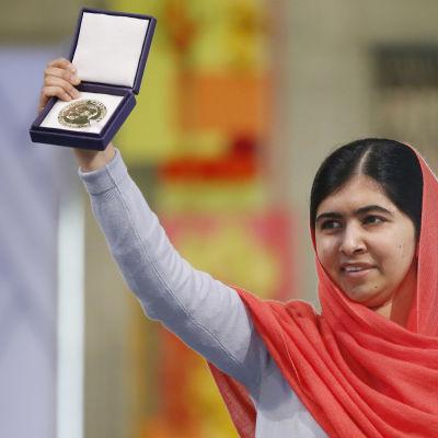 Malala Yousafzai håller upp sin Nobel-medalj