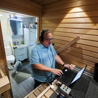 Petteri Löppönen tekee radiolähetystä kotonaan saunassa. Taustalla hänen Harry-koiransa.