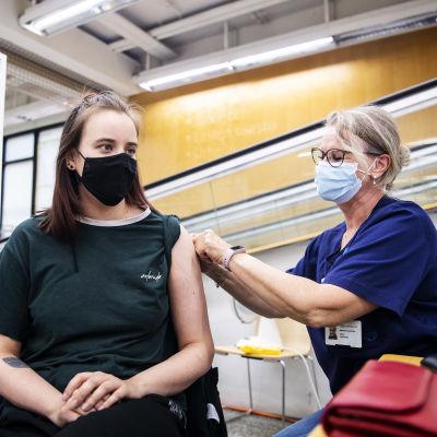 En ung person klädd i svar med långt ljusbrunt hår får sin första vaccindos.