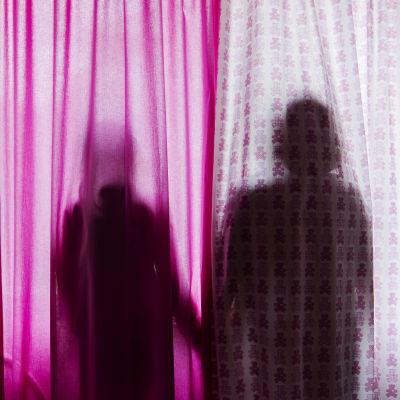 Anonyymissä valokuvassa lapsi ja äiti seisovat verhon takana.