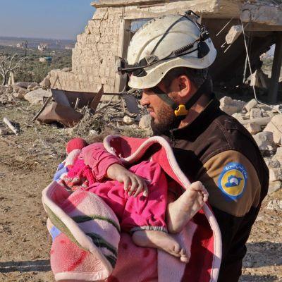 En medlem av frivilligkåren Vita hjälmarna bär på ett barn som räddats ur rasmassor i Maaret Misrin, Idlib, efter torsdagens flygattack utförd av syriska regeringsstyrkor.