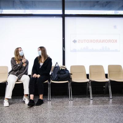 Två unga kvinnor sitter sitter på en bänkrad, iförda munskydd.