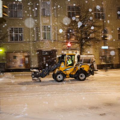En plogtraktor kär på vägen framför ett grönt höghus i Helsingfors centrum.