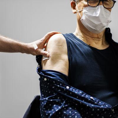 Erkki Partanen, en äldre man i svartbågade glasögon, får coronavirusvaccin.