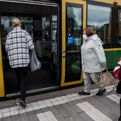 Personer stiger ombord på en spårvagn i Helsingfors centrum den 14 april 2021.