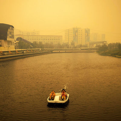 Pariskunta polkuveneilee joessa sankan savun aiheuttaman sumun keskellä.