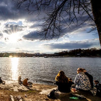 Ihmisiä Siltasaaressa nauttimassa auringosta.