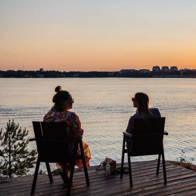 Kaksi henkilö katseleen auringonlaskua Espoon Hanasaaressa.