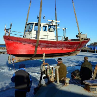 En fiskebåt lyfts ner i vattnet