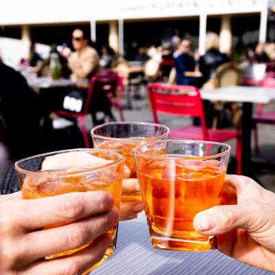 Ystävykset nauttivat Spritzer juomaa ravintolan terassilla.