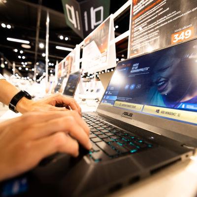 Kodinkoneliikkeen myyjä esittelee tehokasta kannettavaa tietokonetta.