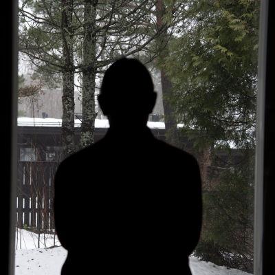 Henkilö katsoo ulos ikkunasta.