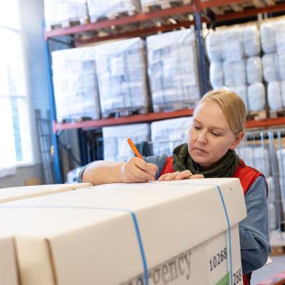 Nainen kirjoittaa laatikkoon SPR:n logistiikkakeskuksen varastossa